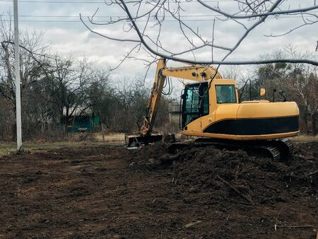 Excavator uprooting trees on land in countryside. Bulldozer clearing land from old trees, roots and branches with dirt and trash. Backhoe machinery. Yard work 스톡 콘텐츠 - 147203054
