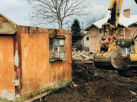 Excavator destroying brick house on land in countryside. Bulldozer clearing land from old bricks and concrete from walls with dirt and trash. Backhoe machinery ruining house
