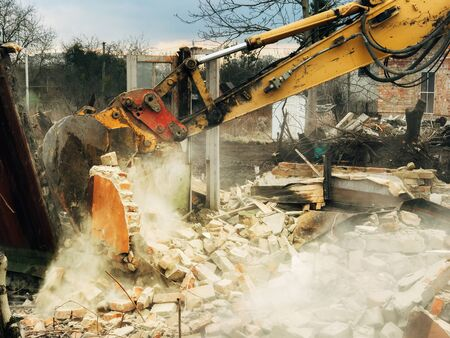 House crushing and collapse. Excavator destroying brick house on land in countryside. Bulldozer clearing land from old bricks and concrete from walls with dirt and trash. Ruining house