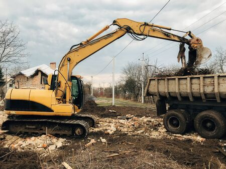 Bulldozer clearing land from old bricks and concrete from walls with dirt and trash. Backhoe machinery ruining house. Excavator destroying brick house on land in countryside. 스톡 콘텐츠 - 147203410