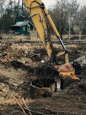 Excavator uprooting trees on land in countryside. Bulldozer clearing land from old trees, roots and branches with dirt and trash. Backhoe machinery. Yard work 스톡 콘텐츠 - 147203526