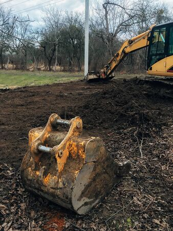 Excavator uprooting trees on land in countryside. Bulldozer clearing land from old trees, roots and branches with dirt and trash. Backhoe machinery. Yard work