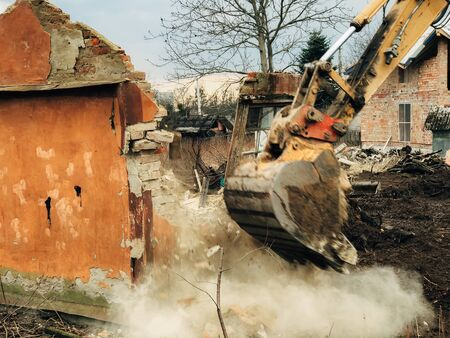 House crushing and collapse. Excavator destroying brick house on land in countryside. Bulldozer clearing land from old bricks and concrete from walls with dirt and trash. Ruining house 스톡 콘텐츠 - 147199713