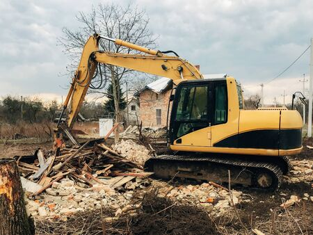 Bulldozer clearing land from old bricks and concrete from walls with dirt and trash. Backhoe machinery ruining house. Excavator destroying brick house on land in countryside.
