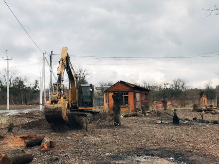 Excavator uprooting trees on land in countryside. Bulldozer clearing land from old trees and branches with dirt and trash. Backhoe machinery. Yard work 스톡 콘텐츠