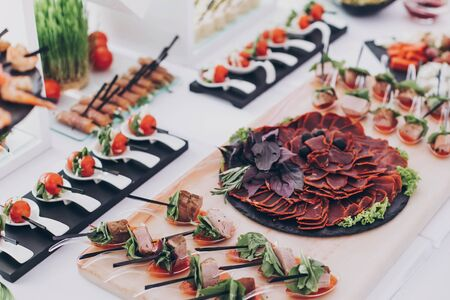 Delicious appetizer and canape on table at wedding reception in restaurant. Luxury catering service. Italian delicatessen, prosciutto snacks, cheese and olives. Christmas feast