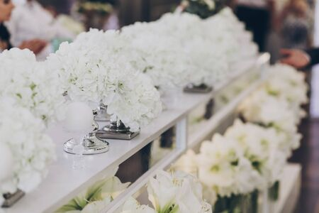Modern decor at wedding reception in restaurant. Stylish white hydrangea and modern white candles with light at tables. Luxury catering