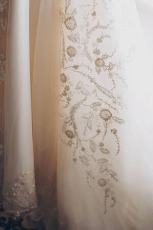 Stylish luxury beige wedding gown with lace floral pattern in light. Close up. Modern wedding dress hanging at window in soft morning light. Bridal morning preparations and boudoir