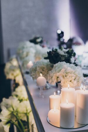 Modern decor at evening wedding reception in restaurant. Stylish white hydrangea and modern white candles with light at tables. Luxury catering