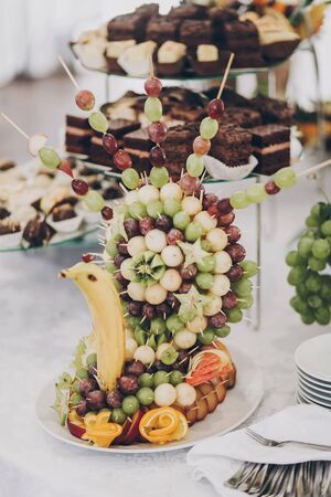 Delicious fresh fruits arranged in bird shape on table at wedding reception in restaurant. Luxury catering service. Wedding healthy fruit bar. Banana, oranges,grapes,peach, and apples 版權商用圖片