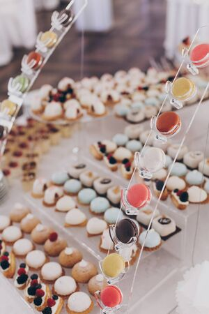 Wedding candy bar. Delicious creamy desserts with fruits, macarons, cakes and cookies on table at wedding reception in restaurant. Luxury catering service. 版權商用圖片