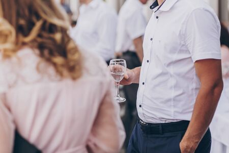 Man holding champagne glass, toasting at wedding reception or corporate party outdoors. Toast for new happy wedding couple. Guests cheering with glasses 版權商用圖片