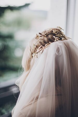 Stylish bride with golden tiara with butterflies and veil, morning preparations for wedding day. Back view. Bride in hair salon styling her hair with modern authentic wreath 版權商用圖片