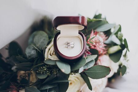 Marriage and divorce concept. Silver wedding rings and stylish modern wedding bouquet of pink roses and green eucalyptus on white soft tulle. Wedding arrangements