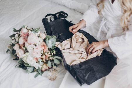 Bride opening box for morning boudoir before wedding ceremony. Modern wedding bouquet, perfume bottle, and gift box with silk robe on white bed.  Wedding arrangements or bridal shower