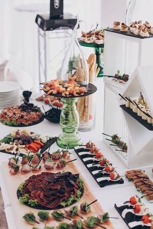 Christmas table feast. Delicious Italian delicatessen, prosciutto snacks, cheese and olives, appetizers on table at wedding reception in restaurant. Luxury catering service