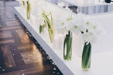 Modern decor at evening wedding reception in restaurant. Stylish white lily flowers and modern white candles with light at tables. Luxury catering