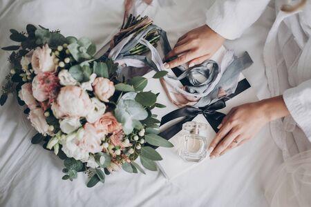 Modern wedding bouquet, perfume bottle, and gift box on white bed. Bride holding white box for morning boudoir before wedding ceremony. Wedding arrangements or bridal shower