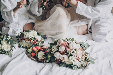 Modern wedding bouquets, wedding rings and delicious macarons on white bed on background of bride and bridesmaids celebrating. Wedding preparations or bridal shower.