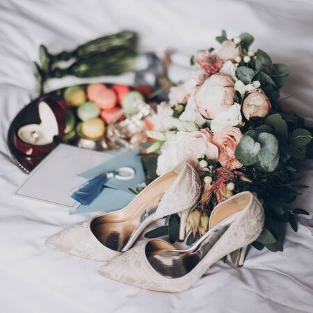 Wedding preparations or bridal shower. Modern wedding bouquet, wedding rings, stylish invitation, perfume bottle, shoes, delicious macarons and green glasses for champagne on white bed.