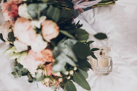 Modern wedding bouquet and perfume bottle. Stylish bouquet of pink roses and green eucalyptus and beige luxury fragrance on white bed. Wedding morning arrangements. Stock Photo