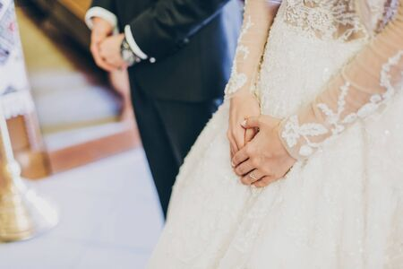 Bride and groom hands close up during holy matrimony in church. Wedding spiritual ceremony. Bride hands on luxury gown. Wedding couple praying