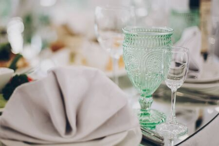 Wedding luxury table setting at reception in restaurant. Stylish glasses for wine, plate with napkin, cutlery and food on tables. Luxury catering service. Christmas feast 版權商用圖片