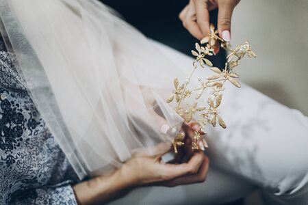 Stylish bride holding golden tiara with butterflies, morning preparations for wedding day. Bride in hair salon styling her hair with modern authentic wreath