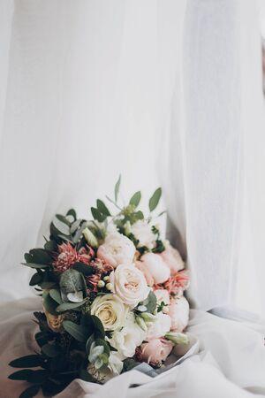 Modern wedding bouquet. Stylish wedding bouquet of pink roses and green eucalyptus on white soft tulle close up. Wedding arrangements and floristics 版權商用圖片