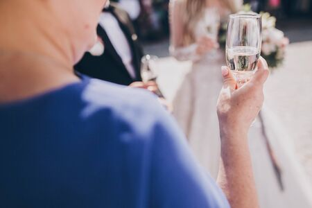 Senior woman holding champagne glass, toasting at wedding reception outdoors. Mother pronouncing toast for new happy wedding couple. Guests cheering with glasses 版權商用圖片