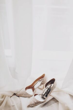 Modern wedding shoes on tulle in soft morning light. Stylish luxury beige shoes with lace floral pattern on window. Bridal morning preparations and boudoir