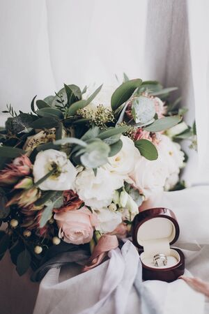Modern wedding bouquet and wedding rings. Silver wedding rings and stylish bouquet of pink roses and green eucalyptus on white soft tulle. Wedding arrangements. Marriage and divorce concept 版權商用圖片