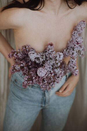 Blooming lilac flowers covering naked woman upper body on rustic background. Woman posing with lilac branches in denim jeans. Creative moody image. Sensuality and tenderness concept Banque d'images - 147996796