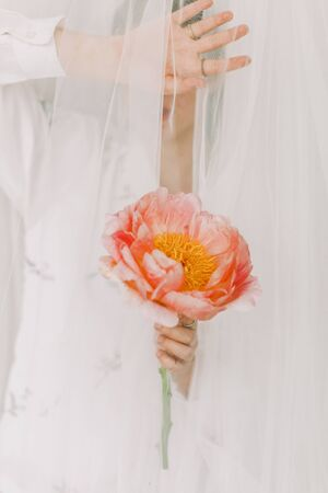 Aesthetic sensual image of beautiful woman behind veil holding pink peony. Stylish girl under tulle gently holding peony flower in hand with jewelry. Soft image