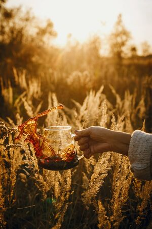 Coffee splash and drops in sun. Hand spilling out fresh hot coffee from glass flask in sunny warm light in rural herbs. Alternative coffee brewing in travel. Atmospheric tranquil moment. Banque d'images