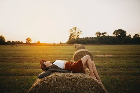 Stylish girl relaxing on hay bale in summer field in sunset. Young woman in hat resting on hay in sunshine, atmospheric tranquil moment. Countryside slow life 免版税图像