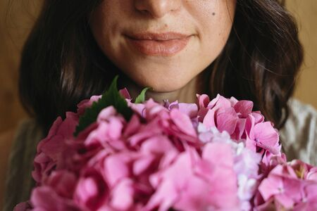Young woman smelling beautiful hydrangea bouquet on background of  rustic wood. Girl holding pink and purple hydrangea flowers, cropped view. Beautiful scent