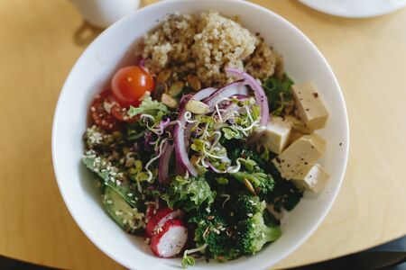Buddha bowl. Delicious vegan meal, bowl with avocado, radish, broccoli, tofu, tomato, couscous, microgreen and sesame seeds. Healthy eating concept. Top view 免版税图像