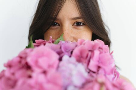 Young woman smelling beautiful hydrangea bouquet on background of white wall. Stylish girl holding pink and purple hydrangea flowers. Happy mothers day or womens day.