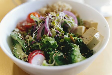 Buddha bowl. Delicious vegan meal, bowl with avocado, radish, broccoli, tofu, tomato, couscous, microgreen and sesame seeds. Healthy eating concept