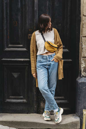 Stylish hipster girl standing at building in european city street. Young woman in casual fashionable outfit posing at old wooden door. Alone leisure activity in city