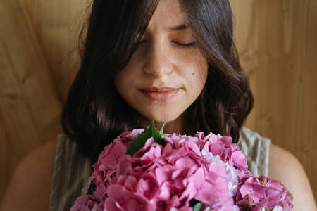 Young woman smelling beautiful hydrangea bouquet on background of  rustic wood. Stylish girl holding pink and purple hydrangea flowers. Happy mothers day or womens day.