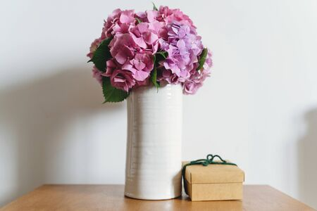 Hydrangea bouquet in vase and gift box on background of white wall with copy space. Beautiful pink and purple hydrangea flowers at home. Happy mothers day