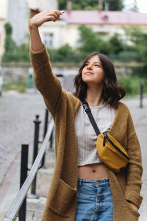 Young woman in casual fashionable outfit taking selfie while walking  in city street. Stylish hipster girl holding phone and chatting online.  Social communication