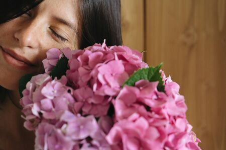 Young woman smelling beautiful hydrangea bouquet on background of  rustic wood. Stylish girl holding pink and purple hydrangea flowers. Beautiful scent