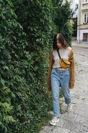 Young woman in casual fashionable outfit walking at green bush wall in city street.Stylish hipster girl walking in european street.  Alone leisure activity in city