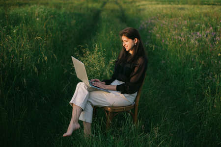 Fashionable elegant girl working on laptop and sitting on rustic chair in green summer field. New office concept. Remote work with social distancing and safety protocols