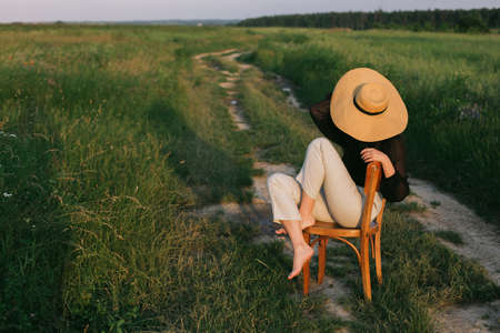 Fashionable young woman relaxing in field, tranquil moment. Creative image. Summer countryside. Stylish elegant girl in straw hat sitting on rustic chair in summer meadow in evening.