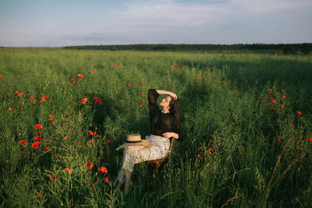 Fashionable young woman relaxing in field in evening light. Creative beautiful image. Slow living. Stylish elegant girl sitting on rustic chair in summer meadow with flowers.