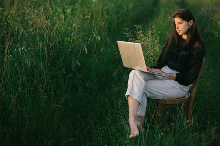 Fashionable elegant girl working on laptop and sitting on rustic chair  in summer field at sunset. Young business woman working online. Freelance and remote work outdoors. Creative image